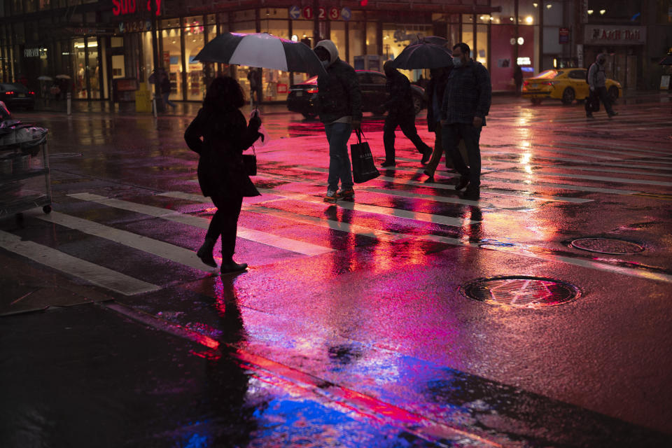 Shoppers walk in a rainstorm, Monday, Nov. 30, 2020 in New York. With people staying home as virus cases surge, Cyber Monday is expected to be the biggest online shopping day yet, bringing in nearly $13 billion in one day. (AP Photo/Mark Lennihan)