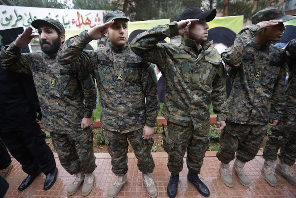 In this December 4, 2013 photo, Hezbollah fighters salute during the funeral procession of Hassan al-Laqis, a senior commander for the Lebanese militant group Hezbollah, who was gunned down, at his hometown in Baalbek city, east Lebanon. The Shiite group has sent hundreds of its fighters into Syria to shore up President Bashar Assad's overstretched troops, helping them gain ground around the capital, Damascus, and near the Lebanese border. But with its own casualties mounting in a civil war that activists say has killed more than 150,000 people in three years, officials say Hezbollah has turned to a variety of new tactics - including complicated commando operations - to hunt down rebels and opposition commanders. (AP Photo/Hussein Malla)
