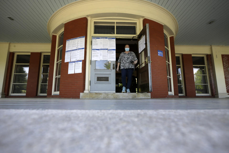 Voter Christina Tremblay, of Providence, R.I., steps out of a voting station at the historic Casino function hall at Roger Williams Park, Tuesday, June 2, 2020, in Providence. In-person voting is being offered at a reduced number of locations for voters who missed the deadline to request a mail ballot. (AP Photo/Steven Senne)