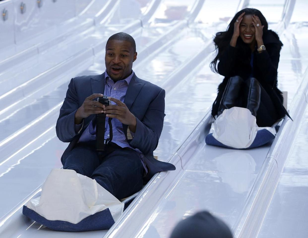 Atlanta Falcons defensive end Osi Umenyiora, left, and his fiancee, Miss Universe 2011 Leila Lopes, right, slide down the toboggan slide during Super Bowl Boulevard festivities Wednesday, Jan. 29, 2014, in New York. The Seattle Seahawks are scheduled to play the Denver Broncos in the NFL Super Bowl XLVIII football game on Sunday, Feb. 2, in East Rutherford, N.J. (AP Photo/Julio Cortez)
