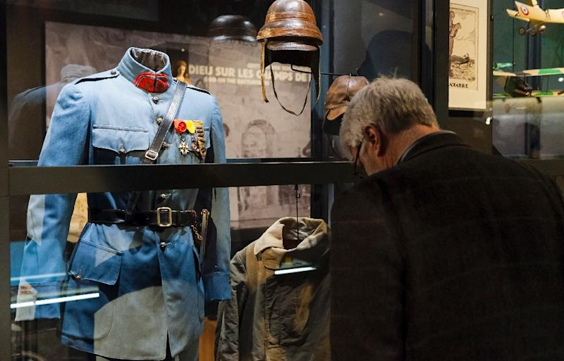 A visitor looks at uniforms and equipment displayed for an exhibition to commemorate the 1916 Battle of Verdun in the redesigned Memorial of Verdun in Fleury-devant-Douaumont, France on February 12, 2016 (AFP Photo/Jean-Christophe Verhaegen)
