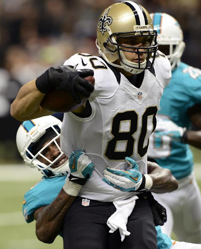 New Orleans Saints tight end Jimmy Graham (80) carries on a touchdown reception as Miami Dolphins strong safety Chris Clemons (30) tries to tackle in the second half of an NFL football game in New Orleans, Monday, Sept. 30, 2013. (AP Photo/Bill Feig)