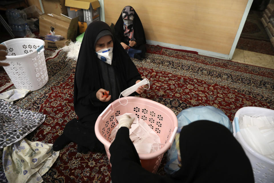 Volunteer women wearing face masks to curb the spread of the new coronavirus prepare face masks, in a mosque in southern Tehran, Iran, Sunday, April 5, 2020. Iran is battling the worst new coronavirus outbreak in the Mideast. (AP Photo/Vahid Salemi)