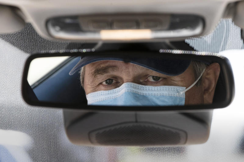 Taxi driver Nicolae Hent, wearing a protective mask, poses for a photograph before before starting work in New York, Monday, April 6, 2020. A taxi driver's job was already tougher in recent years with the arrival of ride-sharing companies such as Uber and Lyft. The empty streets during the coronavirus pandemic have made things more difficult. (AP Photo/Matt Rourke)