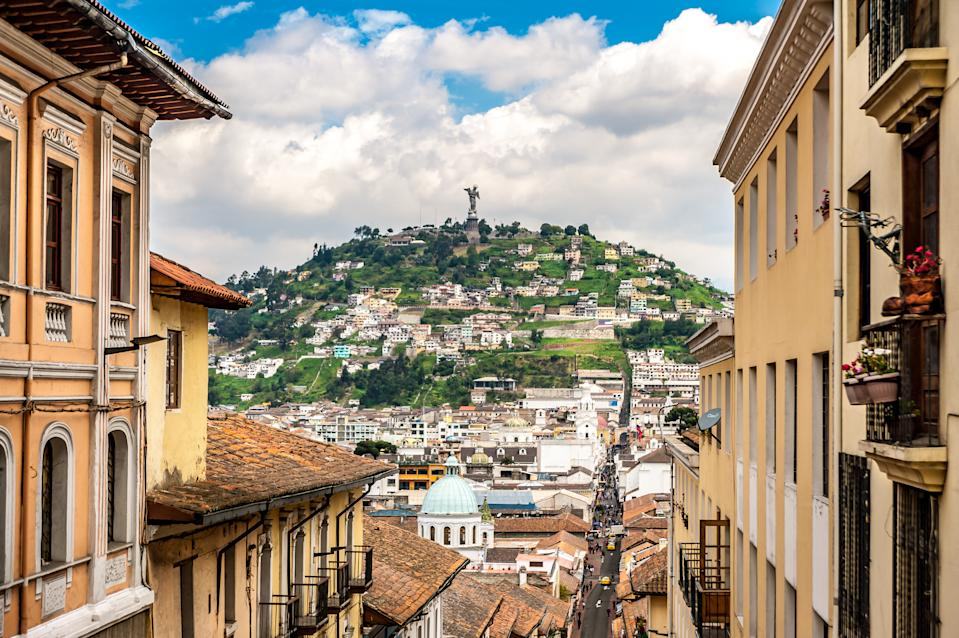 "Quito, Ecuador - May 27th, 2019: View of the historical colonial district of Quito and the 45 meters tall monument of ""Virgin of El Panecillo"" on top of the hill overlooking downtown Quito. The monument was designed by the Spanish artist Agustín de la Herrán Matorras."