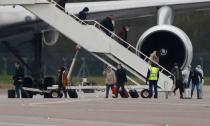 Passengers from China disembark from a plane at RAF Brize Norton near Oxford