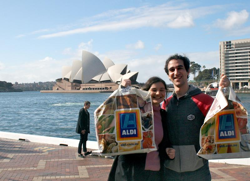Aldi customers Hannah Walker (26) and Mike Weekes (29) stand at the Opera House in Sydney, Australia, 19 July 2015.