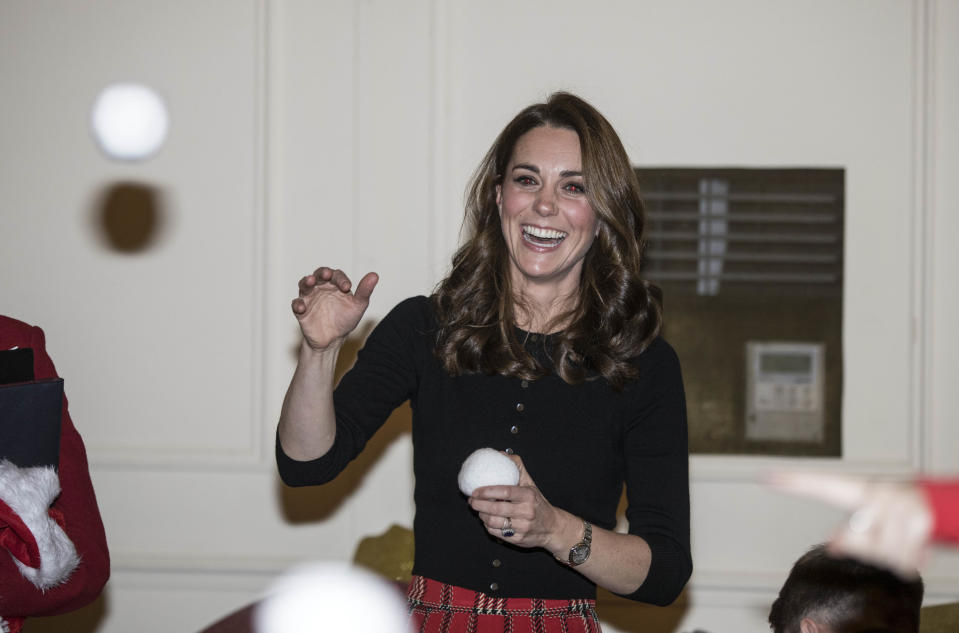 The Duchess of Cambridge enjoys a wintry tradition without the cold as she throws a mock snowball during a children's pretend snowball fight at a Christmas party at Kensington Palace in December 2018. (Richard Pohle - WPA Pool/Getty Images)