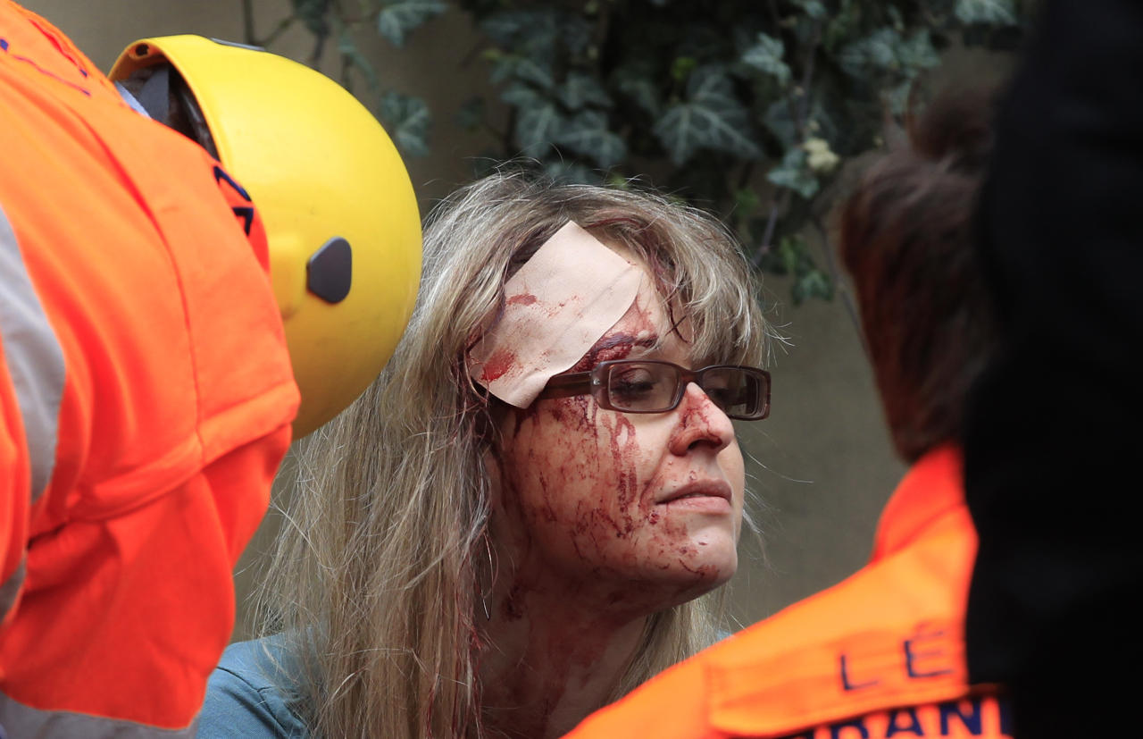 Paramedics help an injured woman after an explosion in downtown Prague, Czech Republic, Monday, April 29, 2013. Police said a powerful explosion has damaged a building in the center of the Czech capital and they believe some people are buried in the rubble. (AP Photo/Petr David Josek)