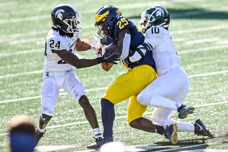Michigan State's Tre Person, left, and Michael Dowell tackle Michigan's Hassan Haskins during the third quarter on Saturday, Oct. 31, 2020, at Michigan Stadium in Ann Arbor.
