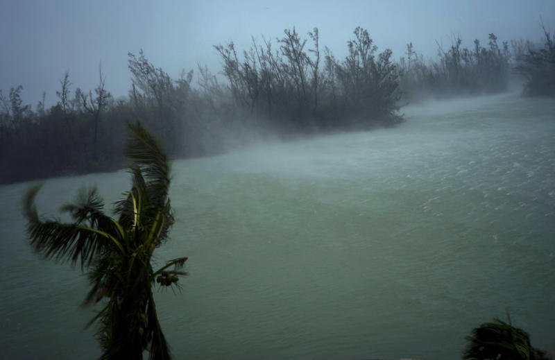 Strong winds from Hurricane Dorian blow the tops of trees and brush while whisking up water from the surface of a canal that leads to the sea, located behind the brush at top, seen from the balcony of a hotel in Freeport, Grand Bahama, Bahamas, Monday, Sept. 2, 2019. Hurricane Dorian hovered over the Bahamas on Monday, pummeling the islands with a fearsome Category 4 assault that forced even rescue crews to take shelter until the onslaught passes. (AP Photo/Ramon Espinosa)