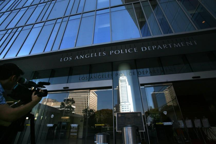 A woman who fell out of a moving Los Angeles police car has reached a settlement with the city and officers.