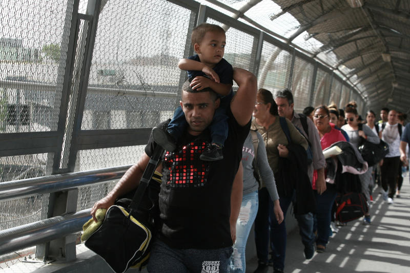 """FILE - In this April 29, 2019 file photo, Cuban migrants are escorted by Mexican immigration officials in Ciudad Juarez, Mexico, as they cross the Paso del Norte International bridge to be processed as asylum seekers on the U.S. side of the border. Mexican Foreign Secretary Marcelo Ebrard said Thursday, Sept. 12, 2019 that Mexico's government doesn't agree with an """"astonishing"""" U.S. Supreme Court order that would block migrants from countries other than Mexico and Canada from applying for asylum at U.S. borders. (AP Photo/Christian Torres, File)"""