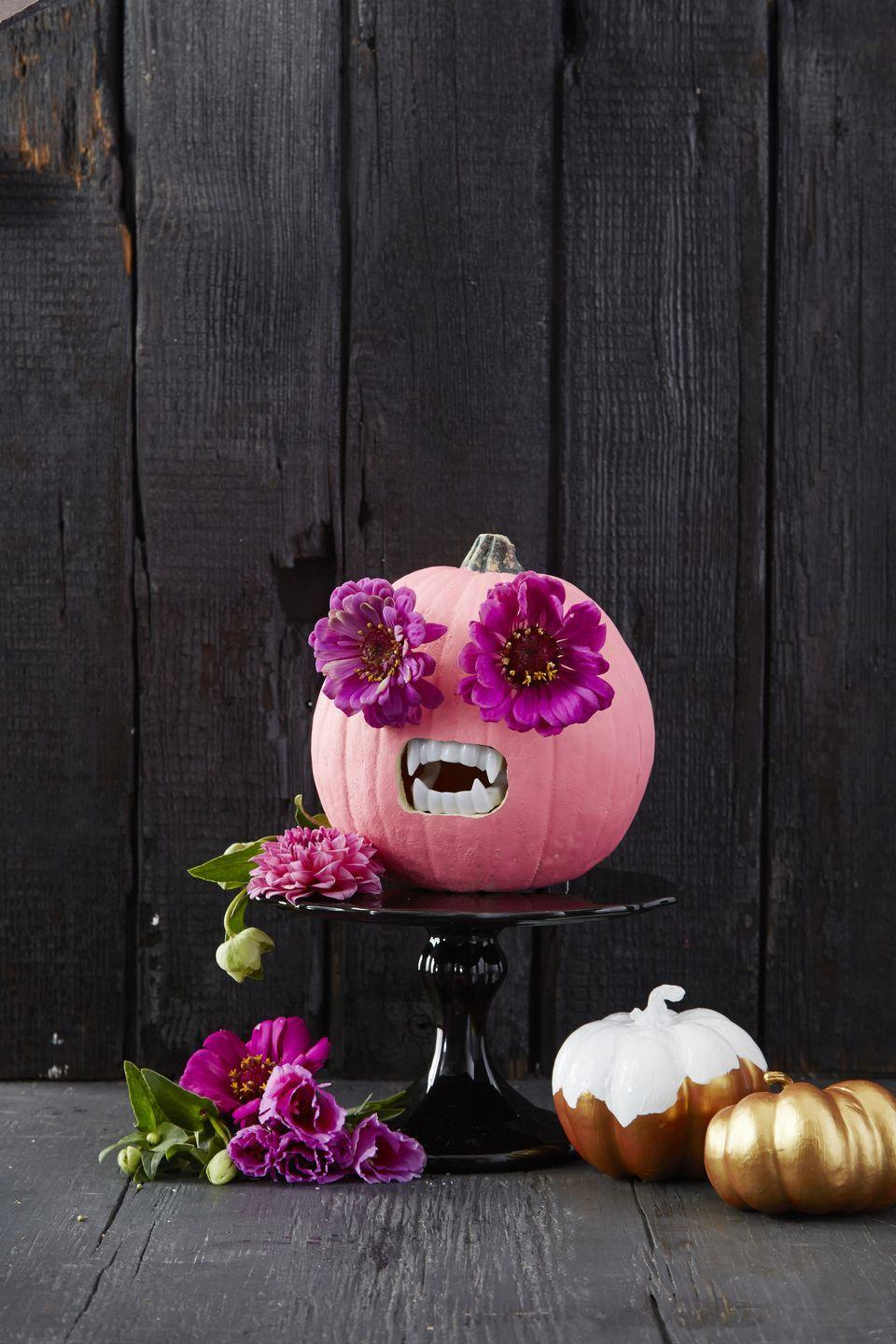 """<p>This idea is perfect the family that wants to make a big statement without spending a ton of time creating their design. All you have to do is paint your pumpkin bright pink (or any color you'd like). Then, just make holes for the eyes and mouth, and pop in some giant faux flowers and scary fake teeth! </p><p><a class=""""link rapid-noclick-resp"""" href=""""https://www.amazon.com/Fun-Express-Plastic-Halloween-Vampire/dp/B005MRN04E/?tag=syn-yahoo-20&ascsubtag=%5Bartid%7C10055.g.238%5Bsrc%7Cyahoo-us"""" rel=""""nofollow noopener"""" target=""""_blank"""" data-ylk=""""slk:SHOP FAKE TEETH"""">SHOP FAKE TEETH</a></p>"""