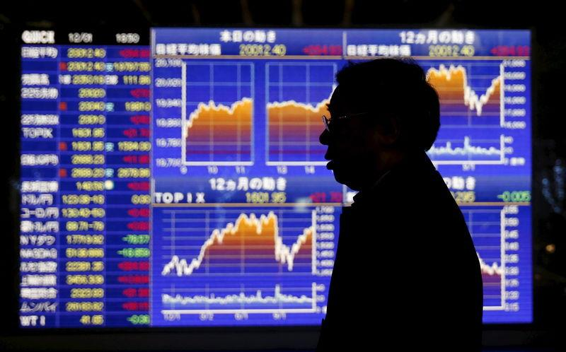 Man walks past an electronic board showing graphs of recent Japan's Nikkei share average outside a brokerage in Tokyo