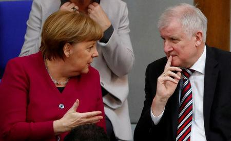 FILE PHOTO: German Chancellor Angela Merkel talks to Interior Minister Horst Seehofer during a session of the Bundestag in Berlin, Germany, March 21, 2018. REUTERS/Fabrizio Bensch/File Photo