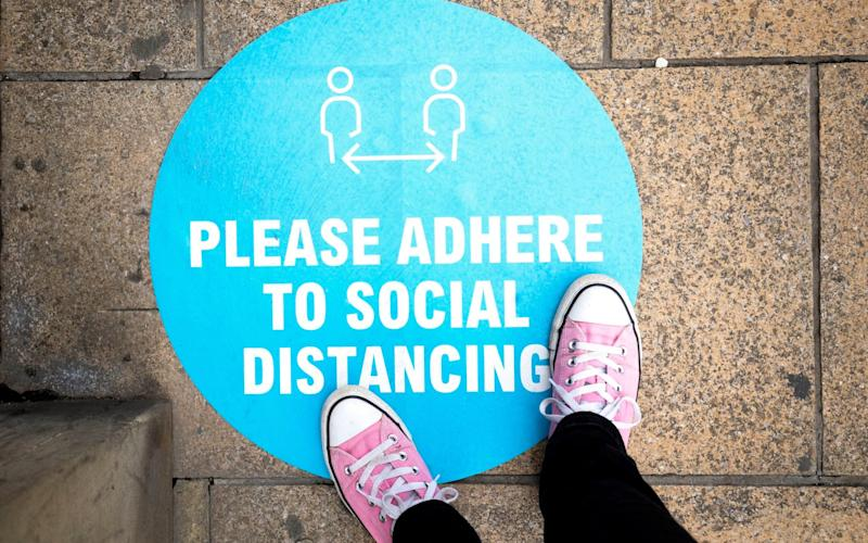 Social distancing sign outside a shop on the pavement in Edinburgh's Princes Street - PA