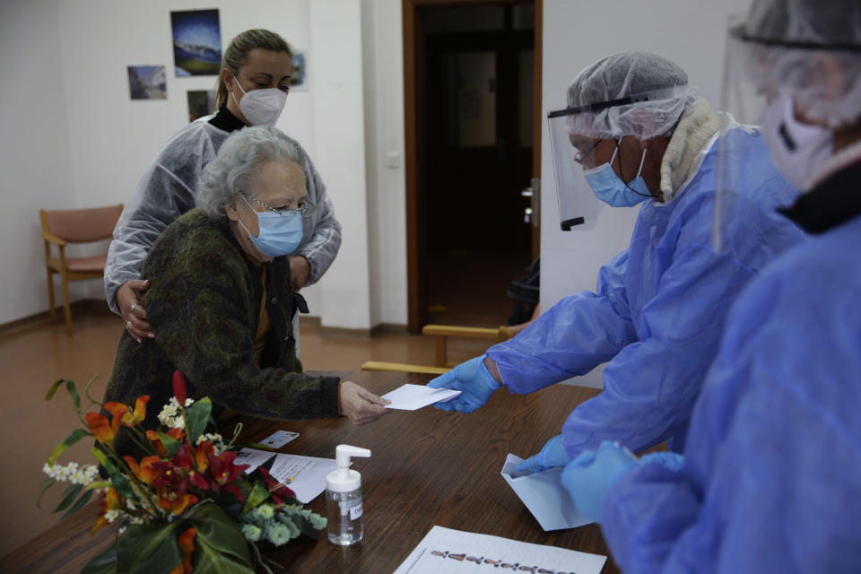 Rosa Gordo, 89, hands her presidential election ballot to municipal workers in protective gear at the elderly care home where she resides in Montijo, south of Lisbon, Tuesday, Jan. 19, 2021. For 48 hours from Tuesday, local council crews are collecting the votes from people in home quarantine and from residents of elderly care homes ahead of Sunday's presidential election. (AP Photo/Armando Franca)