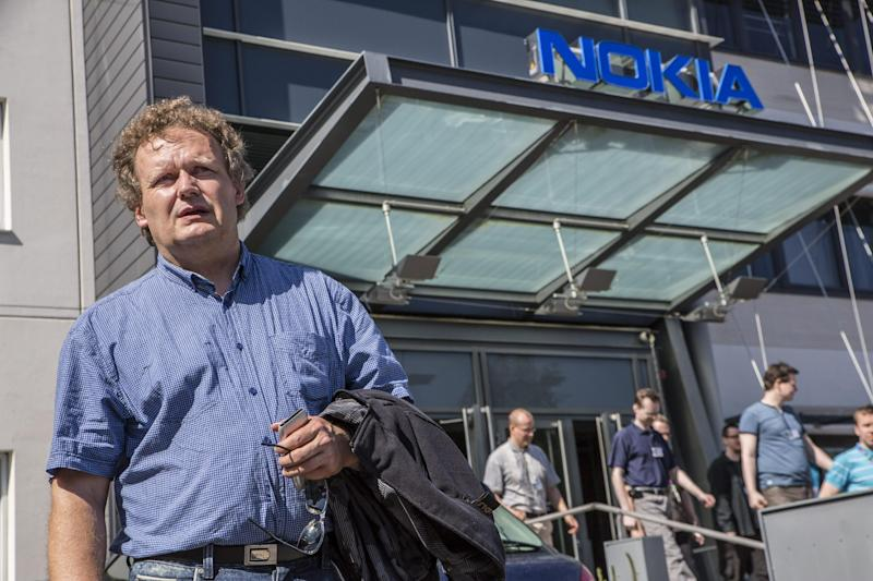 Union steward Jarmo Talvitie talks to media as Nokia employees leave a personnel briefing in Tampere, Finland, Thursday June 14, 2012. Nokia Corp. will lay off 10,000 jobs globally and close plants by the end of 2013, the company said Thursday June 14, 2012, in a further drive to save costs. The cuts mean that it will close some research and development projects, including in Ulm, Germany, and Burnaby, Canada. (AP Photo/Lehtikuva, Jukka Toyli) FINLAND OUT