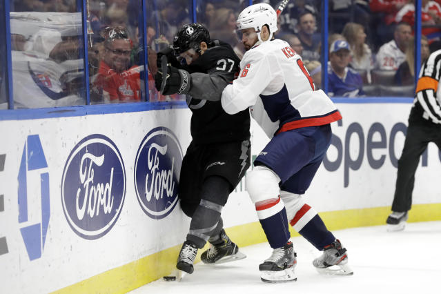 Tampa Bay Lightning center Yanni Gourde (37) is pinned against the boards by Washington Capitals defenseman Michal Kempny (6) during the second period of an NHL hockey game Saturday, Dec. 14, 2019, in Tampa, Fla. (AP Photo/Chris O'Meara)
