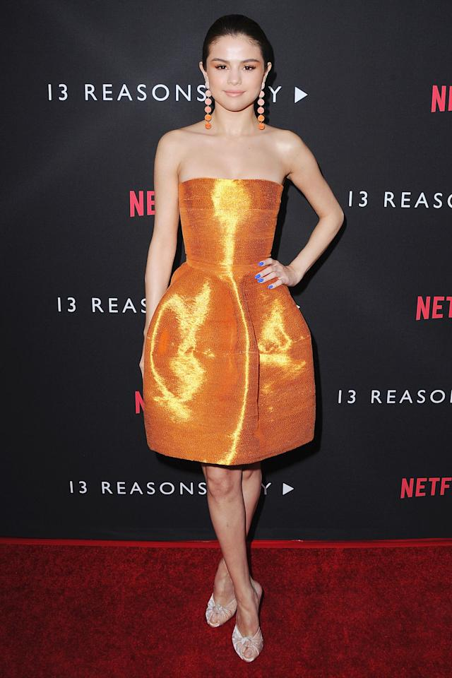 """<p>Who:Selena Gomez<span></span></p><p>When:March 30, 2017<span></span></p><p>What: Oscar de la Renta Dress, Giuseppe Zanotti<span> shoes,</span><a rel=""""nofollow"""" href=""""https://rebeccaderavenel.com/products/chiquita"""">Rebecca de Ravenel earrings</a></p><p>Why:Orange is arguably one of the most difficultcolors to wear on the red carpet. Leave it to Selena Gomez to surpass expectations, wearing a high-shine party dress by Oscar de la Renta to the premiere of<em>13 Resons Why</em>. The true genius of her look, though, is thatshe doubled downon the colorwith matching earrings<em></em>and<em></em><span>eyeshadow, using only herelectric blue manicure to offset it all.</span></p><p><span></span></p>"""