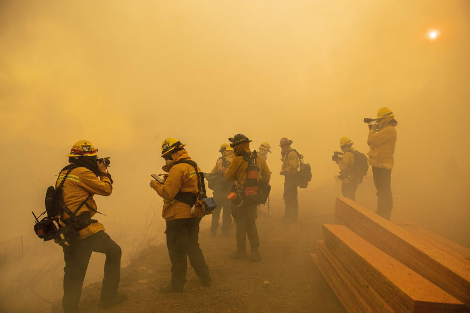 Firefighters with Cal Fire are enveloped in smoke as fire from the Green Fire passes by near homes on Hidden Glen Lane and Hidden Hills Road in Yorba Linda, Calif., Monday, Oct. 26, 2020. (Leonard Ortiz/The Orange County Register via AP)