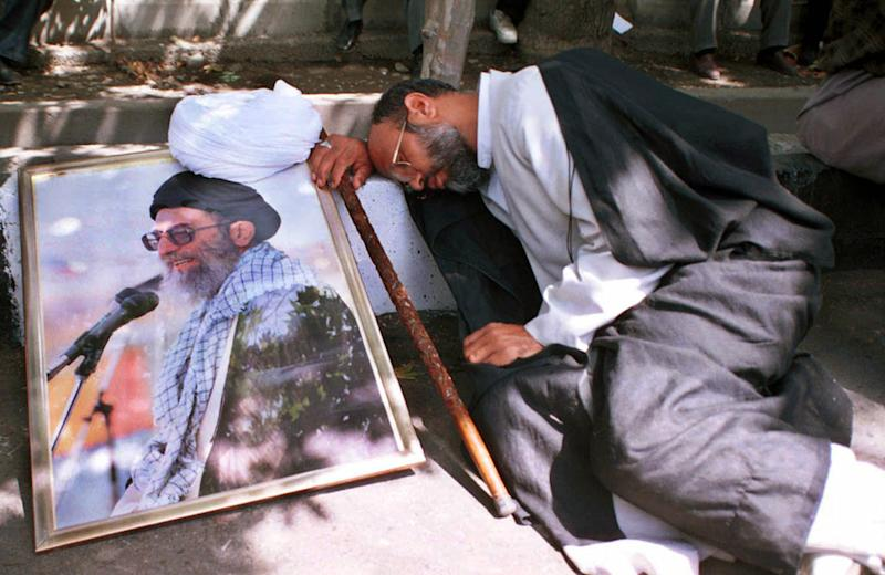 FILE-In this Tuesday, August 8, 2000 file photo, Iranian clergyman Mohammad Azadparvar, who allegedly was injured by chemical weapons in the 1980-88 Iran-Iraq war, rests next to a picture of the supreme leader Ayatollah Ali Khamenei, at a demonstration in front of Iranian parliament in support of the supreme leader Ayatollah Ali Khamenei. For more than a generation, Iranian newspapers regularly post notices: Another veteran of the 1980s' war with Iraq has died of complications from exposure to chemical weapons from Saddam Hussein's arsenal. The claims now that Iran's Syrian allies used similar battlefield tactics, including possibly unleashing sarin gas, forced Tehran's leaders into perhaps their most difficult juncture of the nearly 30-month Syrian civil war: How much to stick by Bashar Assad if the Western allegations are backed by U.N. inspection teams. (AP photo/Vahid Salemi)