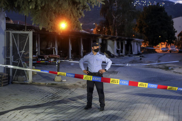 A police officer secures the site of a burned out makeshift hospital following a fire in North Macedonia's northwestern city of Tetovo, Thursday, Sept. 9, 2021. North Macedonia's government has declared three days of mourning after a deadly overnight fire in a COVID-19 field hospital left more than 10 people dead and many injured. The blaze broke out late Wednesday where a hospital had been set up following a recent spike in infections in the region that left local hospitals full. (AP Photo/Visar Kryeziu)