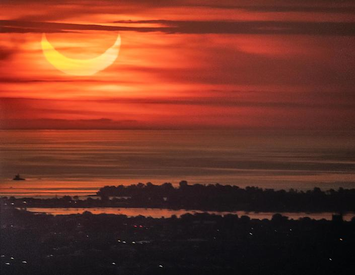 The sun rises over New York City during a solar eclipse on June 10, 2021, as seen from The Edge observatory deck at The Hudson Yards. / Credit: NOAM GALAI / Getty Images