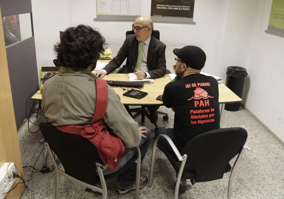 Activists of the Mortgage Victims Platform negotiate with an employee as they occupy a branch of nationalized lender Bankia to protest against home evictions and what they call abusive clauses in mortgage contracts, in central Valencia February 14, 2014. REUTERS/Heino Kalis (SPAIN - Tags: BUSINESS REAL ESTATE CIVIL UNREST)