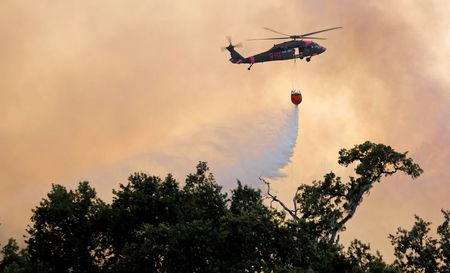 A firefighting helicopter drops water onto a hot spot at the River Fire near Lakeport California