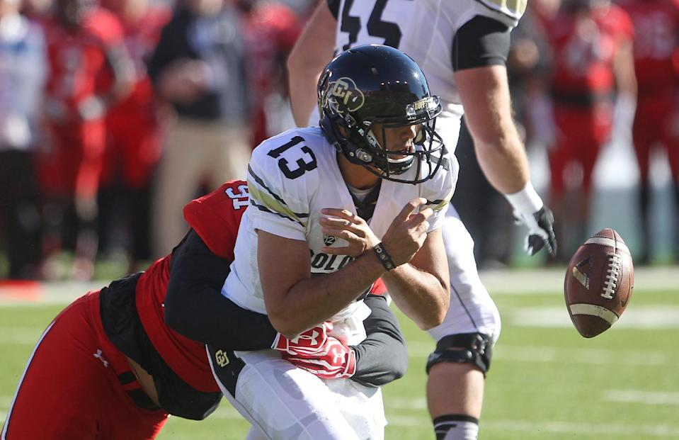 Colorado quarterback Sefo Liufau (13) fumbles the ball as he is sacked by Utah defensive tackle Tenny Palepoi (91) in the first quarter during an NCAA college football game Saturday, Nov. 30, 2013, in Salt Lake City. (AP Photo/Rick Bowmer)