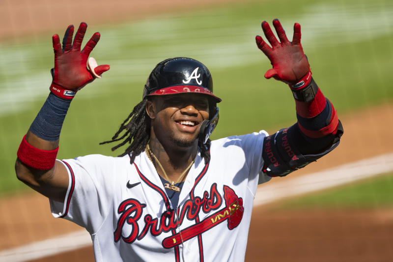 Atlanta Braves' Ronald Acuna Jr. celebrates as he approaches the dugout after a solo home run to center field during the first inning of a double-header baseball game against the Washington Nationals, Friday, Sept. 4, 2020, in Atlanta. (AP Photo/John Amis)