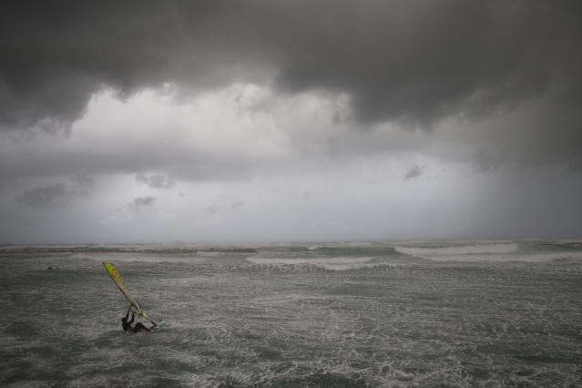 Wind surfers ride on waves in the Mediterranean Sea in Tel Aviv, Israel, Wednesday, Jan. 16, 2019. A harsh weather front brought sandstorms, hail and rain to parts of the Middle East, with visibility down in The Egyptian capital as an orange cloud of dust blocked out the sky. Dusty winds whipped through Israel and the West Bank as well on Wednesday, with hail falling near Tel Aviv and meteorologists announcing that snow was expected later in the day in Jerusalem. (AP Photo/Oded Balilty)