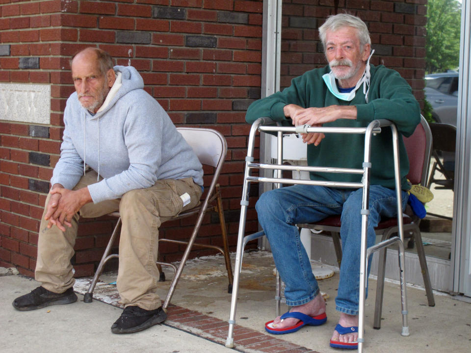 Richard Leoncini, left, and Wayne Krause, right, sit outside a temporary evacuation center in Manville, N.J., on Friday, Sept. 3, 2021. Like many in their neighborhood near the flood-swollen Raritan River, they had to be rescued by boat in the middle of the night as flood waters surged into their apartments. (AP Photo/Wayne Parry)