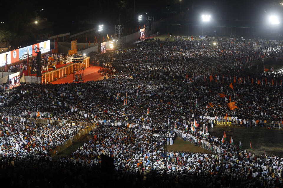 A crowd gathers to watch the swearing-in-ceremony of Shiv Sena party President Uddhav Thackeray as the chief minister of Maharashtra state at Shivaji Park in Mumbai, India, Thursday, Nov. 28, 2019. Supporters of the Nationalist Congress Party (NCP), Congress party and the Shiv Sena alliance thronged the park to watch their leaders take oath of office. (AP Photo/Rajanish Kakade)
