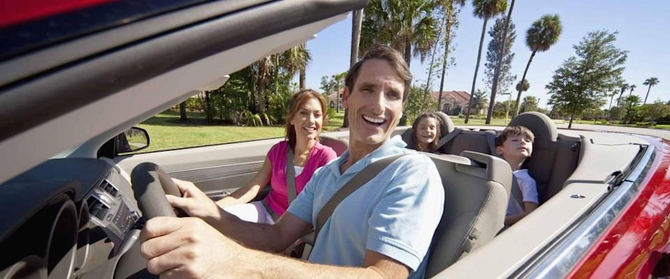 A family of four, mother, father, son and daughter driving in a convertible car on a sunny day in hot location with palm trees