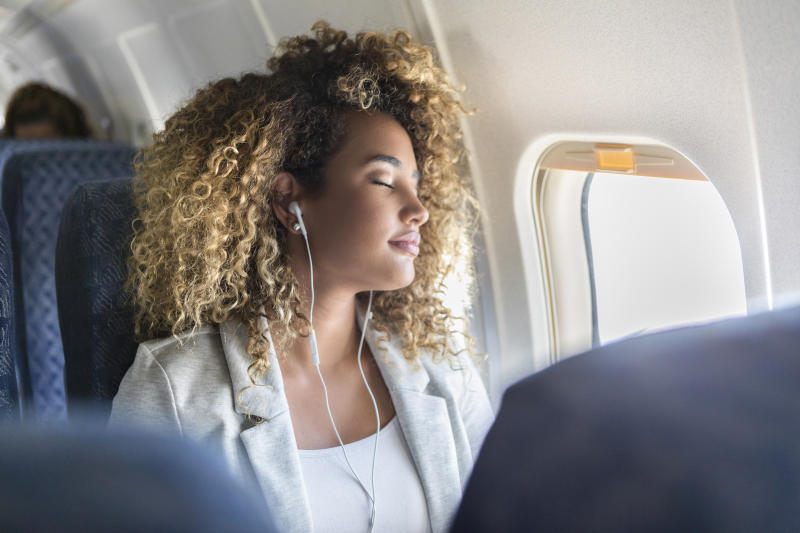 Attractive young woman naps during long airplane flight. She is wearing earbuds.
