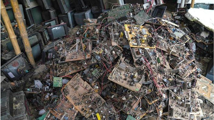 Old TV components are discarded inside at a TV recycling scrap yard in Dhaka