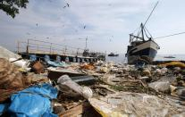Garbage is seen near a fishing boat on Fundao beach in the Guanabara Bay in Rio de Janeiro March 13, 2014. According to the local media, the city of Rio de Janeiro continues to face criticism locally and abroad that the bodies of water it plans to use for competition in the 2016 Olympic Games are too polluted to host events. Untreated sewage and trash frequently find their way into the Atlantic waters of Copacabana Beach and Guanabara Bay - both future sites to events such as marathon swimming, sailing and triathlon events. REUTERS/Sergio Moraes (BRAZIL - Tags: ENVIRONMENT SPORT OLYMPICS)