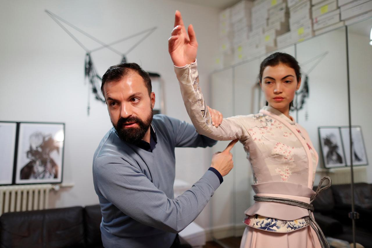 French designer Julien Fournie (L) adjusts a creation on model Daphne (R) during a fitting at his workshop ahead of his Spring-Summer 2018 Haute Couture fashion show presentation in Paris, France, January 15, 2018. Picture taken January 15, 2018.  REUTERS/Charles Platiau