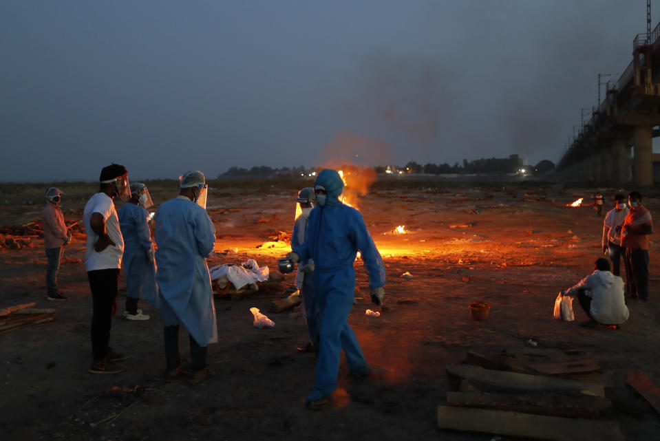Relatives stand near the funeral pyre of their loved one who died due to COVID-19 at a cremation ground in Prayagraj, India, Saturday, May 8, 2021. (AP Photo/Rajesh Kumar Singh)
