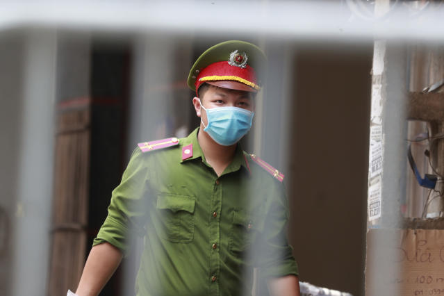 A police officer guards the barricaded entrance of an alley where one of its residents is suspected to have COVID-19 in Hanoi, Vietnam on Wednesday, July 29, 2020. Vietnam intensifies protective measures as the number of locally transmissions, starting at a hospital in the popular beach city of Da Nang, keeps increasing since the weekend. (AP Photo/Hau Dinh)