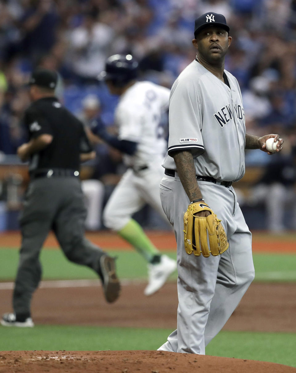 New York Yankees starting pitcher CC Sabathia, right, walks behind the mound as Tampa Bay Rays' Avisail Garcia runs the bases after hitting a home run during the second inning of a baseball game Saturday, May 11, 2019, in St. Petersburg, Fla. (AP Photo/Chris O'Meara)