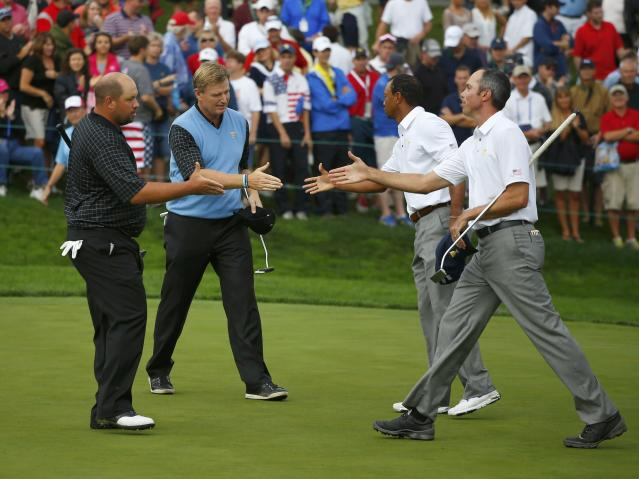 International teammates Ernie Els and Brendon de Jonge shake hands with U.S. teammates Tiger Woods and Matt Kuchar after winning 1 up during the continuation of the rain delayed Foursome matches for the 2013 Presidents Cup golf tournament at Muirfield Village Golf Club in Dublin, Ohio October 6, 2013. REUTERS/Jeff Haynes (UNITED STATES - Tags: SPORT GOLF)