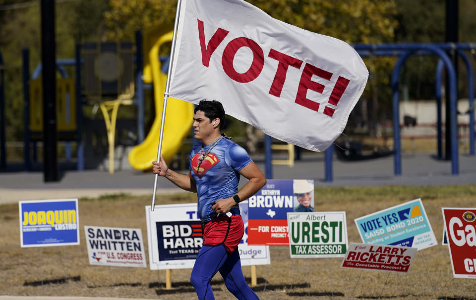 A jogger carries a Vote! flag as he passes a polling station, Tuesday, Nov. 3, 2020, in San Antonio. (AP Photo/Eric Gay)