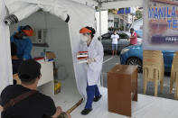 A health worker carries blood samples at a parking lot that has been converted into an extension of the Gat Andres Bonifacio Memorial Medical Center in Manila, Philippines on Monday, Aug. 3, 2020. Philippine President Rodrigo Duterte is reimposing a moderate lockdown in the capital and outlying provinces after medical groups appealed for the move as coronavirus infections surge alarmingly. (AP Photo/Aaron Favila)