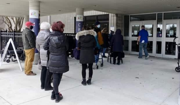 People wait outside the Nepean Sportsplex for their vaccinations. The City of Ottawa says all appointments for the weekend have now been snatched up.