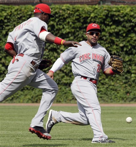 Cincinnati Reds right fielder Xavier Paul, right, and second baseman Brandon Phillips cannot make a play on a single hit by Chicago Cubs' Starlin Castro during the sixth inning of a baseball game in Chicago, Friday, Aug. 10, 2012. (AP Photo/Nam Y. Huh)