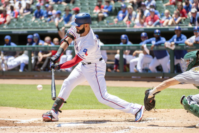 Texas Rangers' Nomar Mazara connects on a sacrifice fly off of Oakland Athletics starting pitcher Paul Blackburn that scored Shin-Soo Choo during the first inning of the first baseball game of a doubleheader Saturday, June 8, 2019, in Arlington, Texas. (AP Photo/Jeffrey McWhorter)